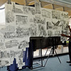 Duron Lewis (front, right) sets up a large mural of his sketches at the Library of Enid and Garfield County Friday, Sept. 13, 2013. An unveiling of the mural revealed drawings by Lewis that depict historical moments in Enid from 1893 to the present time. The mural will be on display at the library as part of the Cherokee Strip Celebration through Sept. 23. (Staff Photo by BONNIE VCULEK)