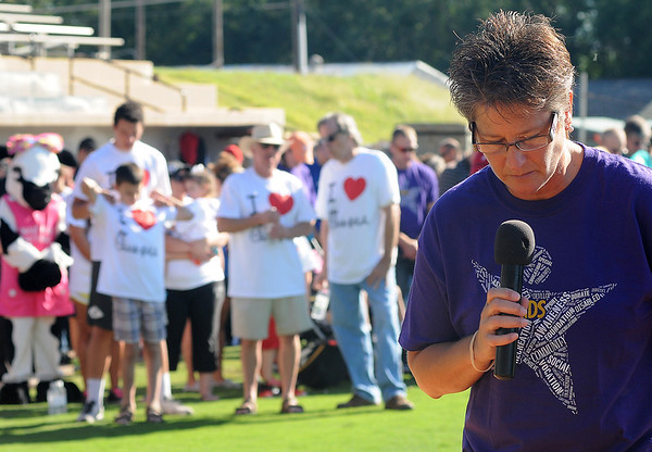 Connie Sturgeon-Hart (right) leads the invocation as her team from Chick-fil-A and others wait for the beginning of the 4RKids Walk at David Allen Memorial Ballpark. The fundraising event supports children and adults with special needs. (Staff Photo by BONNIE VCULEK)