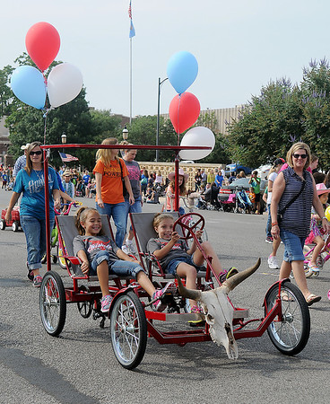 Haylie Cates and Whitly Norris, from Chisholm Elementary School, pedal their contest entry around the square during the Cherokee Strip Celebration Saturday, Sept. 14, 2013. (Staff Photo by BONNIE VCULEK)