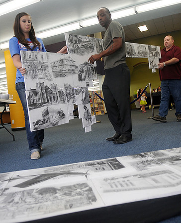 Duron Lewis (front, right) sets up a large mural of his sketches with the help of Jennifer Hargrave (left) and her dad, David, at the Library of Enid and Garfield County Friday, Sept. 13, 2013. (Staff Photo by BONNIE VCULEK)