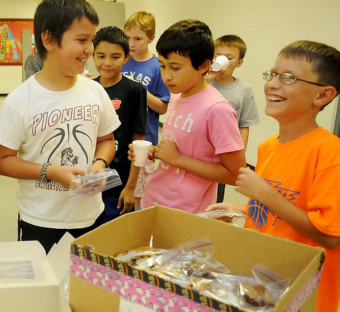 Tabor Watkins (left) labels the treats for his lemonade stand with the help of his 5th grade classmates at Pioneer-Pleasantvale Elementary School Friday, Sept. 13, 2013. For the fifth year, Watkins, who raises funds for St. Jude's, will sell lemonade near the Gazebo on the Garfield County Court House lawn during the Cherokee Strip Parade tomorrow. (Staff Photo by BONNIE VCULEK)