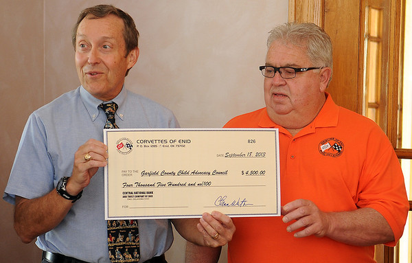 On behalf of the Garfield County Child Advocacy Council, Steve Glasser (left) thanks Rick Wilson (right) and other members of the Corvettes of Enid Club for their generous donation of $4,500 Wednesday, Sept. 18, 2013. (Staff Photo by BONNIE VCULEK)