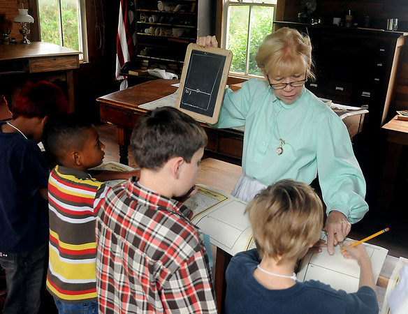 Miss Mary McDonald (left) instructs Garfield Elementary School third grade students during a visit to the U. S. Land Office at Humphrey Heritage Village Friday, Sept. 20, 2013. (Staff Photo by BONNIE VCULEK)