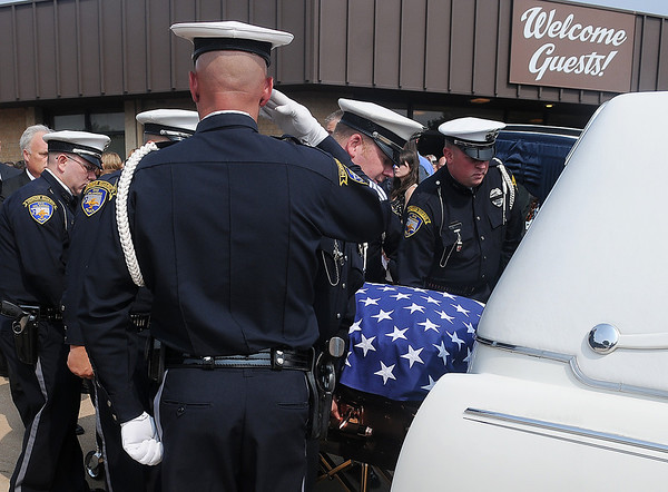"Enid Police Officer Justin Hodges salutes as the EPD Honor Guard escorts the remains of fellow officer, Sgt. Richard Allan ""Rick"" Tanner, II, to a waiting vehicle following a service at Oakwood Christian Church. (Staff Photo by BONNIE VCULEK)"