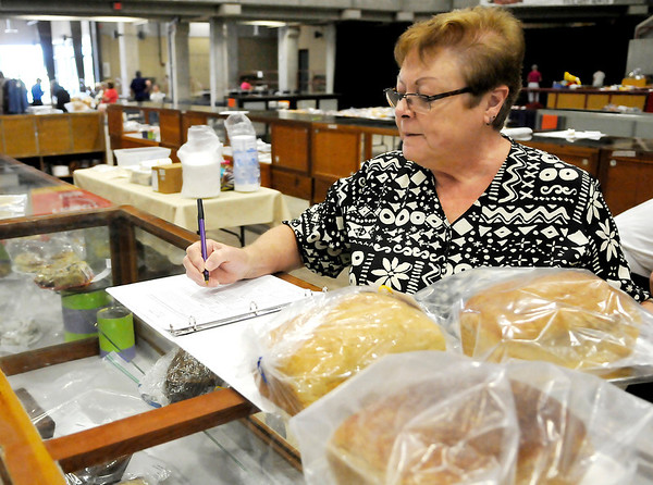 Linda Sader checks in food entries Thursday during the Garfield County Fair inside the Chisholm Trail Expo Center. (Staff Photo by BILLY HEFTON)