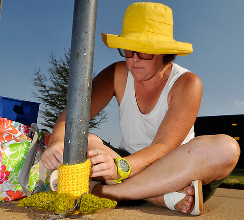 Lisa Magyar attaches a knitted monster foot to a parking meter in front of the post office Thursday during the Yarnover Enid event. (Staff Photo by BILLY HEFTON)