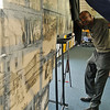 Duron Lewis adjusts the level of his large mural of sketches before it's unveiling at the Library of Enid and Garfield County Friday, Sept., 13, 2013. As part of the Cherokee Strip Celebration, the mural of Lewis's work will remain on display at the library until Monday, Sept. 23. (Staff Photo by BONNIE VCULEK)