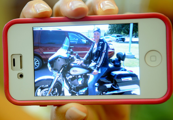 Susanne Lee displays a portrait of herself on her Harley Davidson outside Dexeus Oncology. Lee often rides her motorcycle to the cancer treatment facility at 825 E. Owen K. Garriott Road in Enid. (Staff Photo by BONNIE VCULEK)