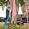 Ty Tompkins and Andrew Shearon fasten knitted blankets around a tree on the Garfield County Courthouse lawn Thursday during the Yarnover Enid event. (Staff Photo by BILLY HEFTON)