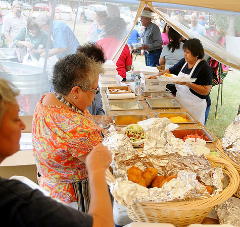 Enid-Intertribal member prepare 800-900 Indian tacos for guests during the opening festivities of the Cherokee Strip Celebration on the Garfield County Court House lawn Friday, Sept. 13, 2013. (Staff Photo by BONNIE VCULEK)