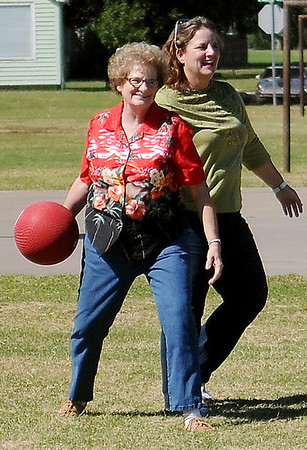 Former Harrison Elementary teacher, Kay Churchill (left) and one of Churchill's students, Cammey Kasper, team up for an outfield catch during a kick ball game at the Harrison Elementary School alumni reunion Saturday, Sept. 21, 2013. The group met for breakfast at Wee Too, toured their old school, played games and had a picnic at Meadowlake Park. (Staff Photo by BONNIE VCULEK)