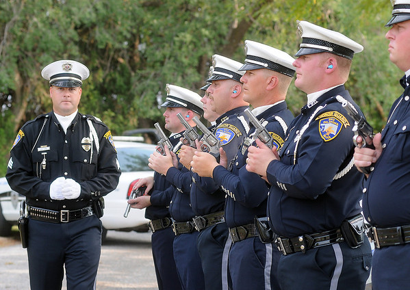 """Sgt. Nick John and other Enid Police Department Honor Guard members complete a 21-gun salute to fellow officer, Sgt. Richard Allen """"Rick"""" Tanner, II, during a special service at Memorial Park Cemetery Saturday, Sept. 14, 2013. Sgt. Tanner, 40, passed away at his home Sept. 7. (Staff Photo by BONNIE VCULEK)"""