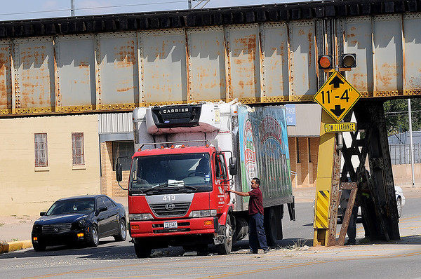 The driver of a Marquez Brothers delivery truck, from Dallas, Tex., approaches the cab of his truck to retrieve his registration and insurance verification after peeling the top of the vehicle back on the bottom of a train overpass on E. Maine Wednesday, Sept. 11, 2013. (Staff Photo by BONNIE VCULEK)