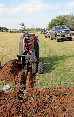 Paul Smith, with the help of a heavy equipment operator, began the trenching for city water for his land along a property easement on N. 16th Street, when his neighbors called the Enid Police Department Friday, Sept. 27, 2013. Smith has faced conflict over his plans to build a new home for his disabled son. (Staff Photo by BONNIE VCULEK)