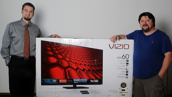 """Scotty Maxwell, director of advertising at Enid News and Eagle, pauses for a portrait with John Holt, from Lahoma, who won the 60"""" Vizio flat screen telivision during the Enid News and Eagle's readers' survey contest drawing. Holt is an appraiser for a firm in Enid. (Staff Photo by BONNIE VCULEK)"""