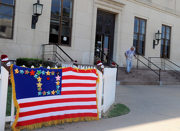 Yarnover Enid creations appear on the fence outside the Garfield County Post Office as a gentleman exits the building with his mail Friday, Sept. 6, 2013. (Staff Photo by BONNIE VCULEK)