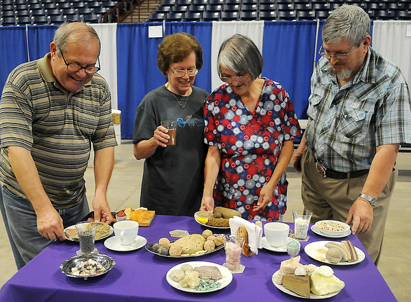 Stan Nowak, Mary Walters, Fay and John Worden, with the Enid Gem and Mineral Society, complete their table setting entry for the Garfield County Fair at the Chisholm Trail Coliseum Wednesday, Sept. 4, 2013. The unique, inedible cuisine features different minerals that resemble items from the different food groups. (Staff Photo by BONNIE VCULEK)
