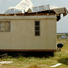 A trailer house and the front porch of the Collins Farm home on East Flynn Road were severely damaged during a thunderstorm's downburst south of Waukomis in Garfield County Monday, Sept. 1, 2014. A large metal building north of the trailer house was also damaged. (Staff Photo by BONNIE VCULEK)