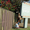 """Carson Conley and Marrisa Hudson roll fresh paint on the fence at the YWCA Saturday, Sept. 20, 2014. Members of Focus 5/6 from Vance Air Force Base and their children provide the labor for the special project as part of """"Keep Enid Beautiful."""" (Staff Photo by BONNIE VCULEK)"""
