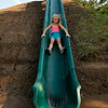Trinity Wall slides down a news slide at Meadowlake Park Tuesday. The slide is located on the south side of the park near the railroad bridge. (Staff Photo by BILLY HEFTON)