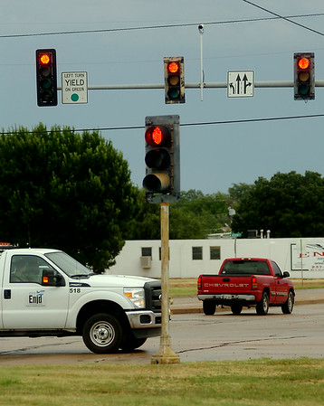 All signal lights flash red at the W. Willow and N. Van Buren intersection as a city of Enid Public Works Division crew travels south on Van Buren Tuesday, Sept. 2, 2014. An early morning storm caused power outages to several signal light locations. Enid Police officers directed heavy traffic at the major intersection and remained on the scene until the temporary 4-way flashing lights could be repaired. (Staff Photo by BONNIE VCULEK)