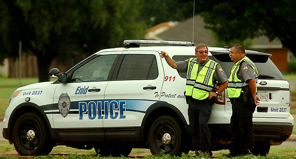 Enid Police Officers Jeff Suttmiller and  Justin Lamle observe traffic flow at the W. Willow and N. Van Buren intersection after an early morning thunderstorm caused signal light failure Tuesday, Sept. 2, 2014. The officers directed heavy traffic until all lights could be reset as a temporary 4-way stop. (Staff Photo by BONNIE VCULEK)