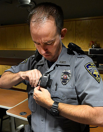 Patrolman John Robinson, of the Enid Police Department, puts on a body camera during a training session Tuesday Seotember 13, 2016 at the Enid Police Department. (Billy Hefton / Enid News & Eagle)