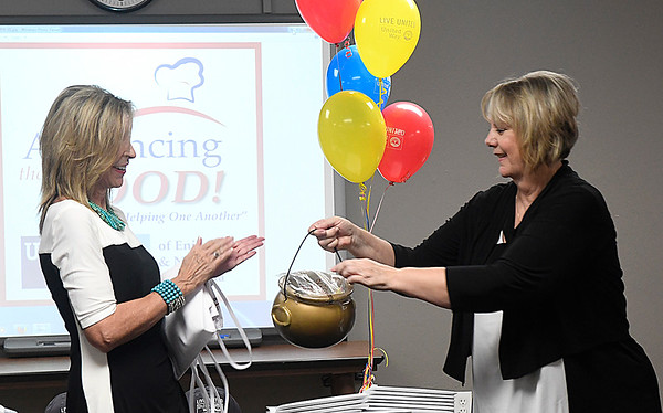 Elaine Johns (right), of Advance Pierre Foods, hands a pot of cash to Pamala Ballard during a United Way kickoff luncheon Tuesday September 13, 2016 at the Central Fire Station. (Billy Hefton / Enid News & Eagle)