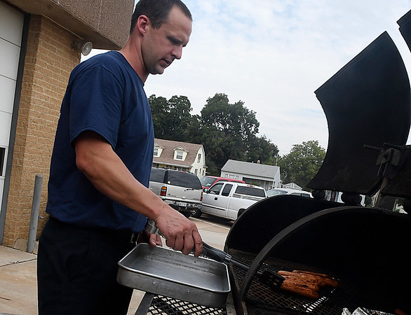 Enid firefighter, Josh Sandwick, cooks hotdogs during a kickoff luncheon for theUnited Way Tuesday September 13, 2016 at the Central Fire Station. (Billy Hefton / Enid News & Eagle)