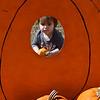 Vivian Herrera peeks through the pumpkin cutout at the Christ United Methodist Church Pumpkin Patch Friday September 30, 2016. (Billy Hefton / Enid News & Eagle)