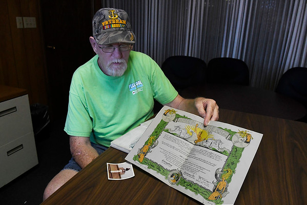 Bob Roberts looks at his Shellback certificate for crossing the equator during an interview September 6, 2017. (Billy Hefton / Enid News & Eagle)