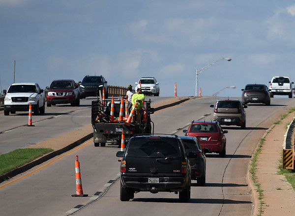 Workers put out traffic cones closing the inside lanes of the north Van Buren overpass Tuesday September 11, 2018. Replacement of the overpass is estimated to take 15 months. (Billy Hefton / Enid News & Eagle)