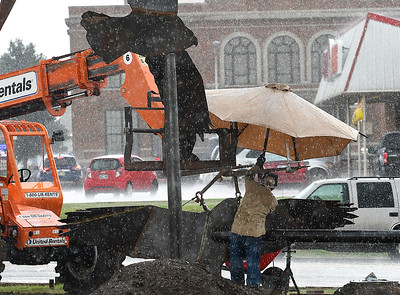 """Michael Mack opens a large umbrella to protect himself from the rain as he works on the art project """"Lazy Circles in the Sky"""" on the northeast corner of Garriott and Independence Thursday, September 12, 2019. (Billy Hefton / enid News & Eagle)"""