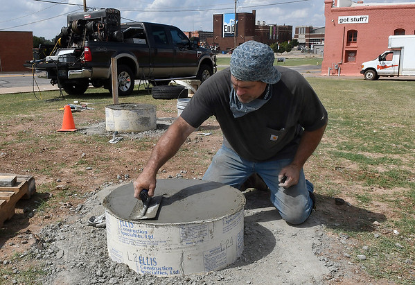 """Michael Mack smooths the top of a pier cap for the art project """"Lazy Circles in the Sky"""" on the northeast corner of Garriott and Independence Tuesday, September 10, 2019. (Billy Hefton / enid News & Eagle)"""