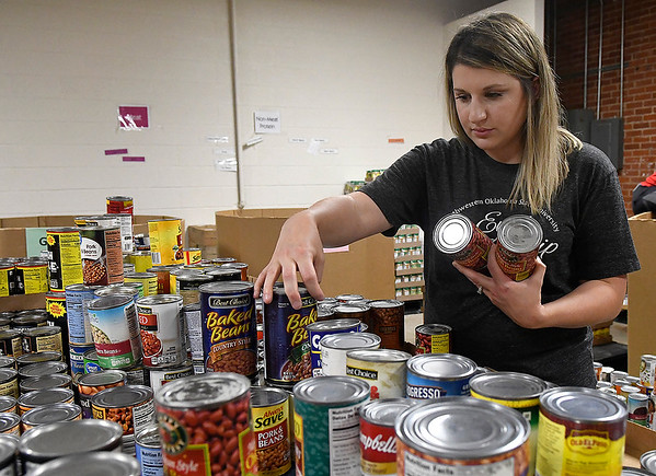Ashley Neal, of the NWOSU Leadership Council, sorts canned goods at Loaves & Fishes Monday, September 30, 2019. (Billy Hefton / Enid News & Eagle)