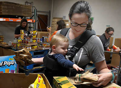 Melissa McKeon and her son, Owen, sort donated food at Loaves & Fishes Monday, September 30, 2019. (Billy Hefton / Enid News & Eagle)