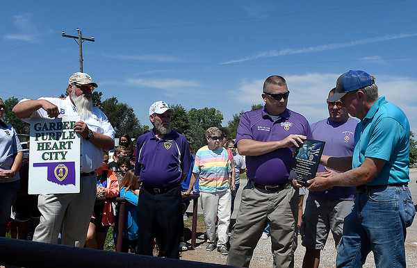 Garber mayor, Warren Dell (right) receives a plaque from James Battles, commander Military Order of the Purple Heart, during a ceremony Friday, September 6, 2019 naming Garber as a Purple Heart City. (Billy Hefton / Enid News & Eagle)