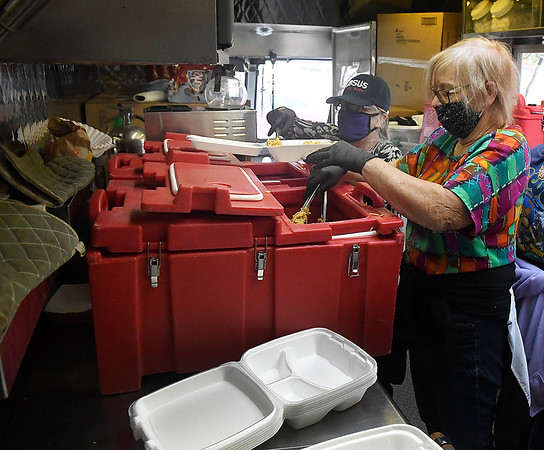 Elaine Epps and Abie carlton fill cartons with food inside the Salvation Army mobile kitchen Friday, September 11, 2020. (Billy Hefton / Enid News & Eagle)