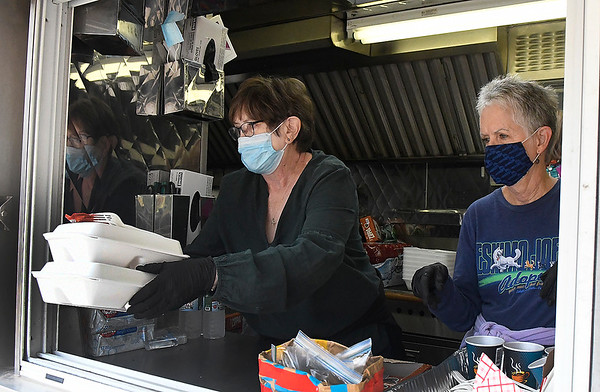 Terri Dally and Karen Storm work the window of the Salvation Army mobile kitchen Friday, September 11, 2020. (Billy Hefton / Enid News & Eagle)