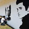 Sean Wills works on a mural of musical legends on the side of Wedding & Banquet Rental Supplies Friday, September 4, 2020. He plans to add more legends to the mural. (Billy Hefton / Enid News & Eagle)