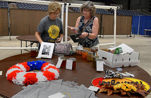 Shirley Clark (left) and Martha Gabriel, from the Pioneer Wheathearts, tag entries for judging in the Garfield County Fair Wednesday, September 8, 2021 at the Chisholm Trail Expo Center. (Billy Hefton / Enid News & Eagle)