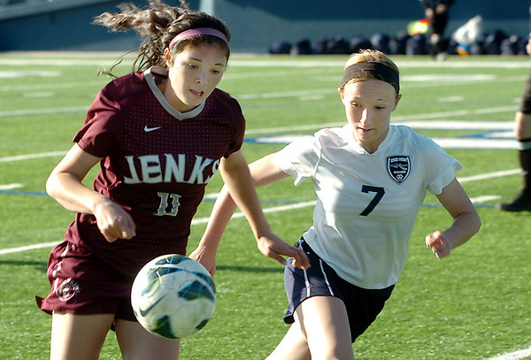 Enid's Shelley Mueller runs with Jenks' Kaylee Dao Thursday at D. Bruce Selby Stadium. (Staff Photo by BILLY HEFTON)
