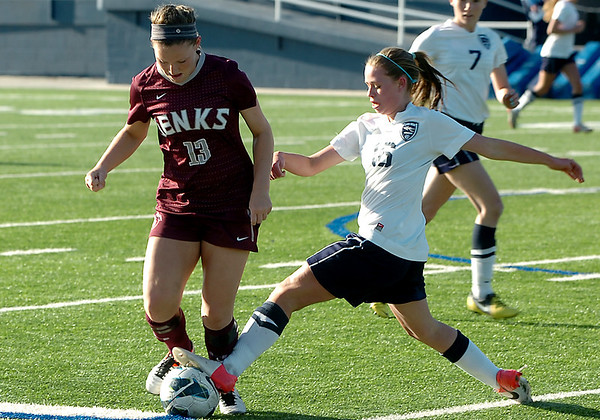 Enid's Kamika Ralstin takes the ball away from Jenks' Lizzie Keester Thursday at D. Bruce Selby Stadium. (Staff Photo by BILLY HEFTON)