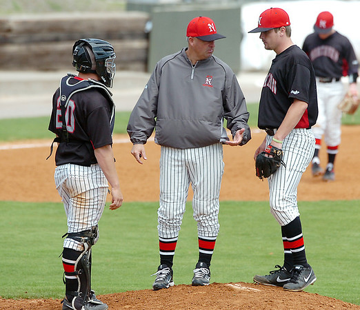 NOC-Enid catcher, Aaron McCandless, stands by as coach Raydon Leaton talks to pitcher, Austin Hannum, during the Jets' game against Redlands CC lunges Monday at David Allen Memorial Ballpark. (Staff Photo by BILLY HEFTON)