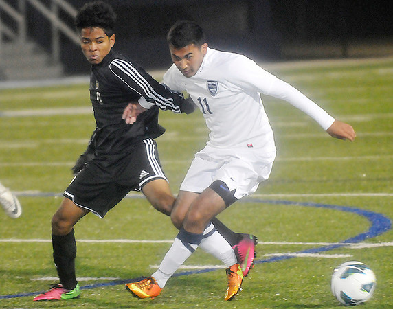 Enid's Felix More locks arms with a Stillwater defender as they struggle to control the ball Tuesday at D. Bruce Selby Stadium. (Staff Photo by BILLY HEFTON)