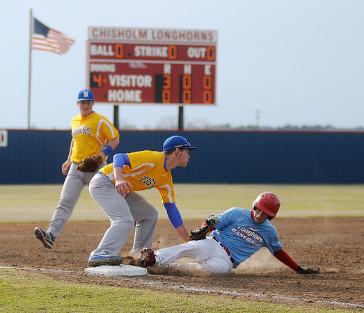 Chisholm's Shane Waggoner slides into third as two Newkirk defenders protect the bag during the district playoffs at Chisholm High School Thursday, April 25, 2013. The Longhorns took a 6-0 lead in the fifth inning in the first game of the double-header. (Staff Photo by BONNIE VCULEK)