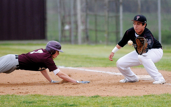 Cashion's Ryan Harrel (left) dives back to first as Pioneer's Jake Mercado anticipates the catch and tag during the OSSAA Class A Regional baseball tournament at Pioneer High School Friday, April 26, 2013. (Staff Photo by BONNIE VCULEK)