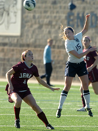 Enid's Shannon Mueller heads the ball Jenks' Madi Medders Thursday at D. Bruce Selby Stadium. (Staff Photo by BILLY HEFTON)