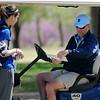 David Lee, Enid High School girls golf coach, glances at Sydney Davenport's score card during the Enid Invitational girls golf tournament at Meadowlake Municipal Golf Course Thursday, April 2, 2015. (Staff Photo by BONNIE VCULEK)