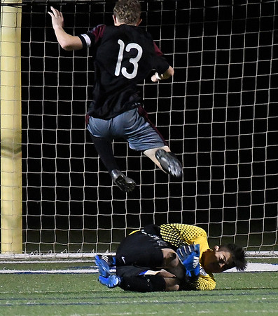 Enid's Angel Neri covers the ball against Owasso Friday April 14, 2014 at D. Bruce Selby Stadium. (Billy Hefton / Enid News & Eagle)